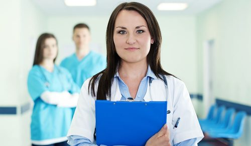 Portrait of young female doctor with interns in background